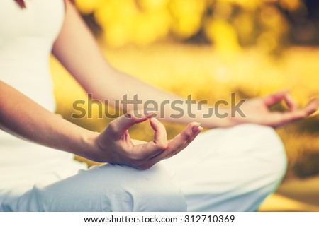 Yoga outdoors in warm autumn sunny park. Woman sits in lotus position zen gesturing. Concept of healthy lifestyle and relaxation - stock photo