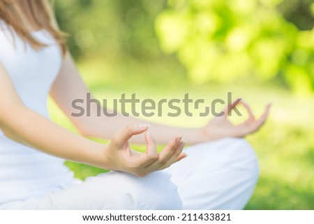 Yoga outdoors. Woman sits in lotus position zen gesturing. Concept of healthy lifestyle and relaxation