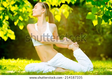 Yoga outdoors. Young healthy beautiful woman is doing a yoga asana in the green park. Concept of healthy lifestyle and relaxation - stock photo