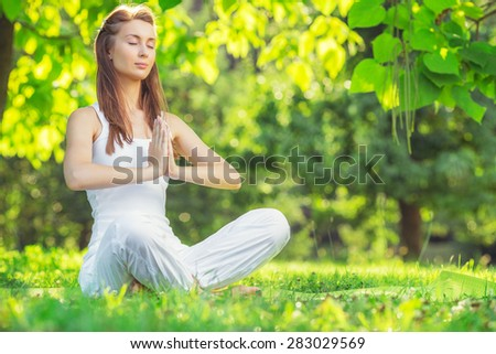 Yoga outdoors. Young woman making namaste symbol. Concept of healthy lifestyle and relaxation. - stock photo