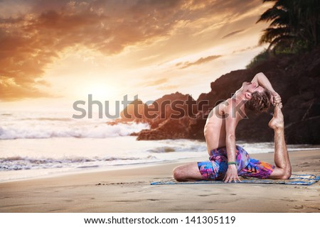 Yoga pigeon pose by man on the sandy beach near the ocean in India - stock photo