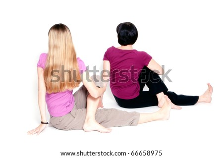 "Yoga pose called ""sitting half spinal twist"" by young and aged woman. - stock photo"