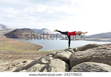 Yoga pose on rocks - stock photo