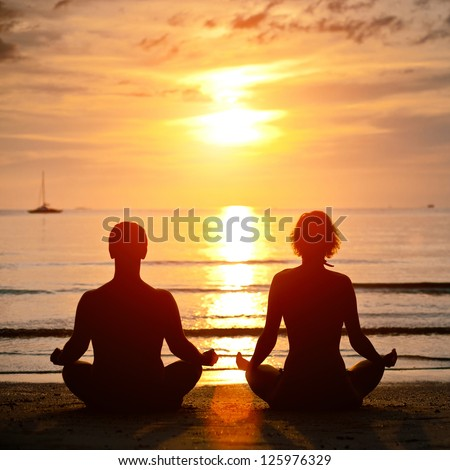 Yoga practice, young couple sitting on the beach of the sea in the lotus position at sunset - stock photo