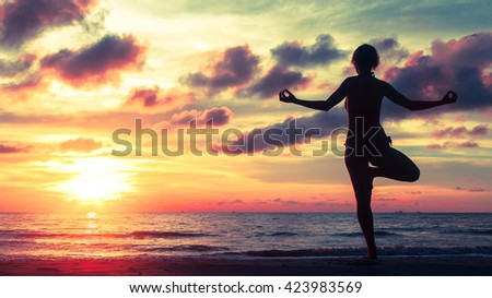 Yoga silhouette at surreal bloody sunset on the sea shore. Calm and self-control. - stock photo