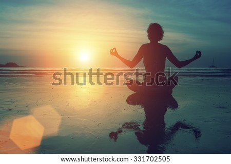 Yoga silhouette meditation girl on the background of the sea and sunset. - stock photo