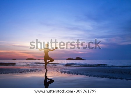 yoga, silhouette of woman on the beach - stock photo
