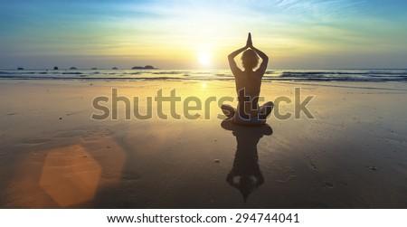 Yoga silhouette. Woman doing meditation near the ocean beach.  - stock photo