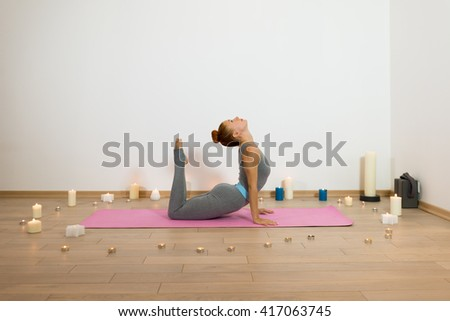Yoga. Slim woman having yoga trainig on pink gymnastic carpet in candle lit room. Yoga concept of physical and mental health, happy living and well being - stock photo