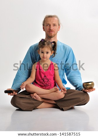 Yoga teacher and a little girl with a singing bowl