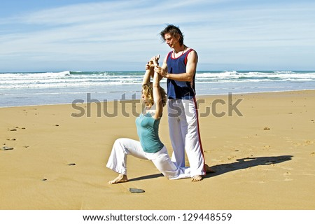 Yoga teacher teaches student yoga on the beach - stock photo
