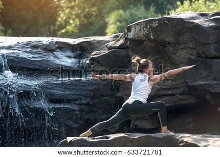 Yoga teachers are practicing on the rocks in the waterfall.