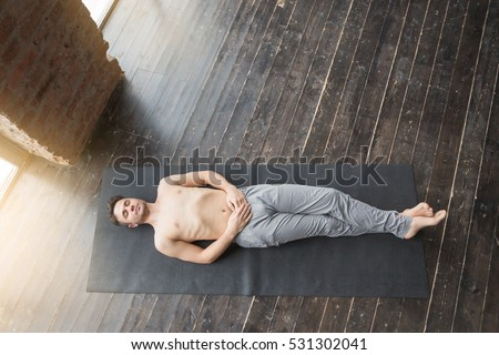 Yoga Top View Of Young Men Meditating On A Wooden Floor And Lying In Shavasana
