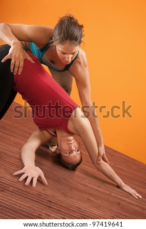 Yoga trainer helping student perform yoga stretching - stock photo