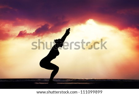 Yoga utkatasana chair pose by woman in silhouette with dramatic sunset sky background. Free space for text - stock photo