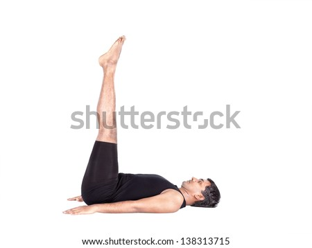 Yoga uttanpadasana pose by Indian man in black costume isolated at white background. Free space for text - stock photo