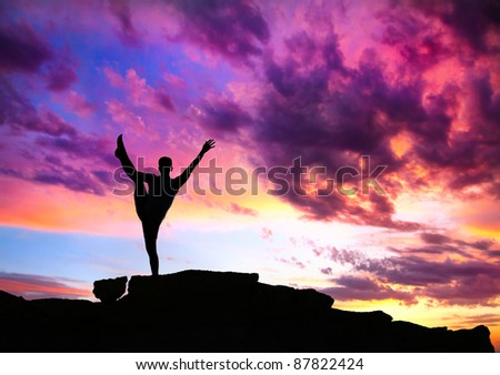 Yoga utthita Hasta Padangustasana balance pose by man silhouette with purple dramatic sunset sky background. Free space for text and can be used as template for web-site - stock photo