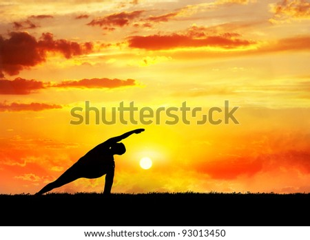 Yoga utthita parsvakonasana horizon pose by man silhouette at sunset sky background. Free space for text and can be used as template for web-site - stock photo