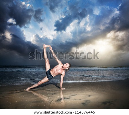 Yoga vasisthasana side plank pose by fit man on the beach near the ocean at sunset background - stock photo