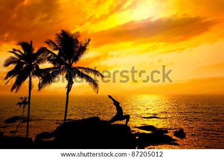 Yoga virabhadrasana I warrior pose by Man in silhouette with palm tree nearby outdoors at ocean and sunset background. Vagator beach, Goa, India. Free space for text - stock photo