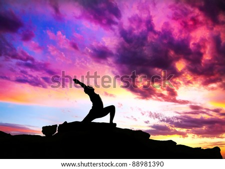 Yoga virabhadrasana I warrior pose by man silhouette with purple dramatic sunset sky background. Free space for text and can be used as template for web-site - stock photo