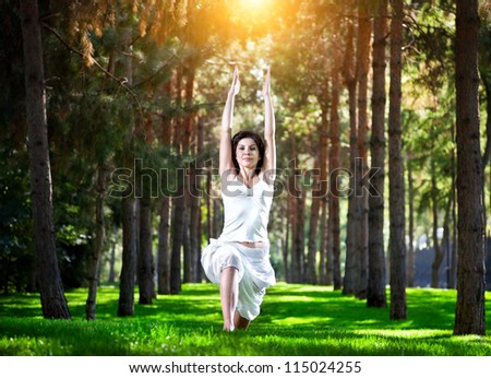 Yoga virabhadrasana I warrior pose by woman in white costume on green grass in the park around pine trees - stock photo