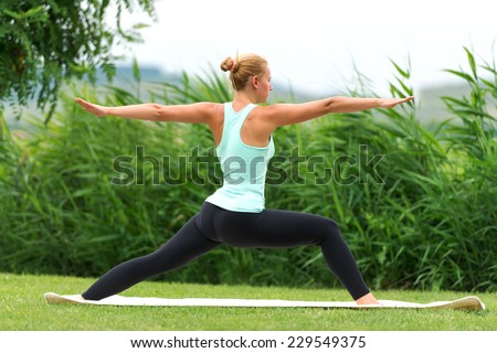 Yoga virabhadrasana II warrior pose by woman - stock photo