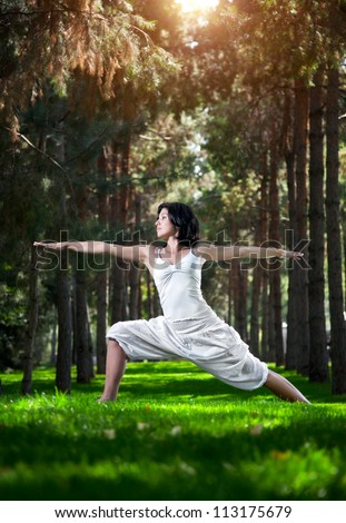 Yoga virabhadrasana II warrior pose by woman in white costume on green grass in the park around pine trees - stock photo