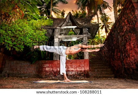 Yoga virabhadrasana warrior III pose by man in white trousers near stone temple at sunset background in tropical forest - stock photo