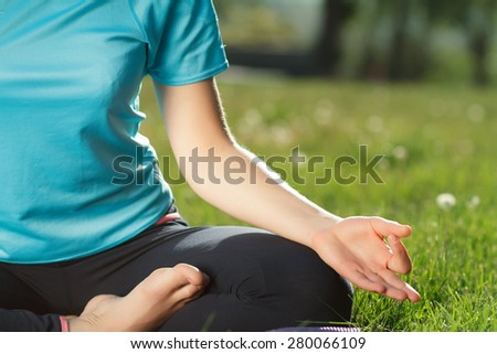 Yoga woman doing exercises lotus in the park - stock photo