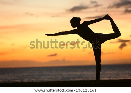Yoga woman in serene sunset at beach doing king dancer pose. Meditation and balance exercise at sunrise or sunset with female yoga instructor exercising outside in nature. - stock photo