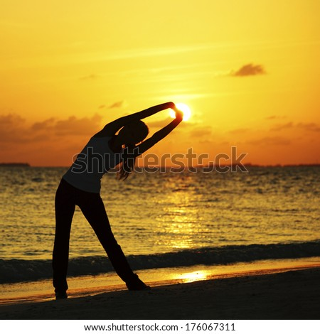 Yoga woman in serene sunset at beach doing stretching workout - stock photo