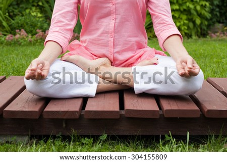 Yoga woman in the garden on the wooden floor - stock photo
