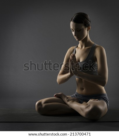 Yoga woman meditate sitting in lotus pose. Silhouette of exercise girl over black background.  - stock photo