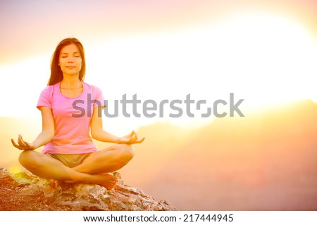 Yoga woman meditating at sunset in Grand Canyon. Female model meditating in serene harmony in lotus position. Healthy wellness lifestyle image with multicultural young woman. From Grand Canyon, USA. - stock photo