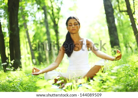 yoga woman on green grass in forest - stock photo
