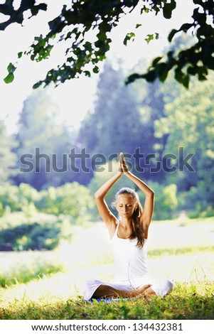 yoga woman on green grass in lotus pose - stock photo