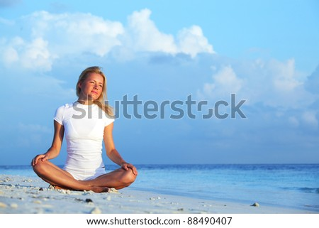 yoga woman on sea coast - stock photo