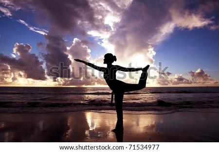 Yoga woman on the beautiful beach at sunrise - stock photo