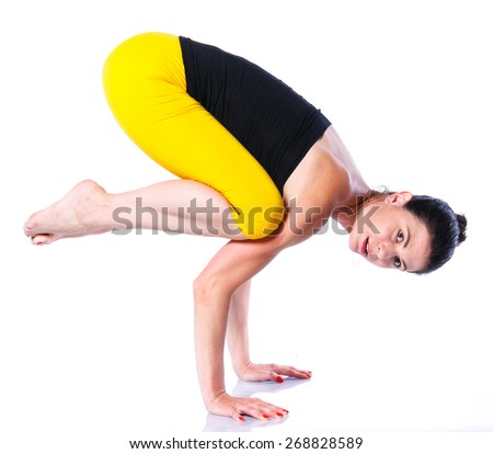 Yoga woman - pretty brunette in active wear doing yoga on white background - stock photo