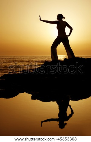 Yoga woman silhouetted against the setting sun with a natural reflection in a rockpool - stock photo