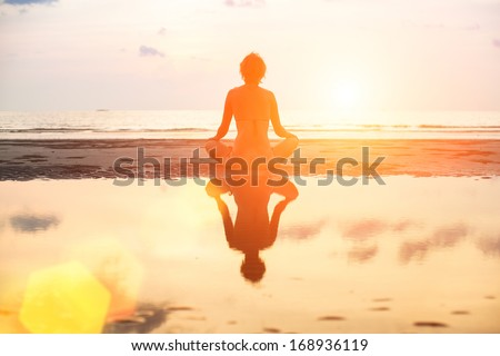 Yoga woman sitting in lotus pose on the beach during sunset, in bright colors with reflection in water. - stock photo