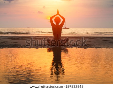 Yoga woman sitting in lotus pose on the beach during sunset with reflection in water. - stock photo