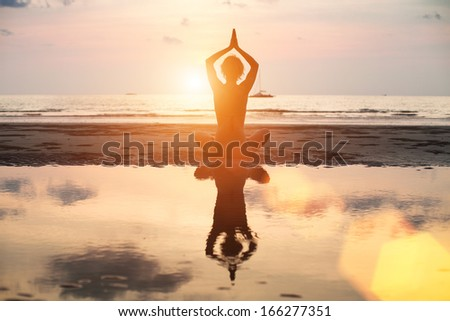 Yoga woman sitting in lotus pose on the beach during sunset, with reflection in water, bright colors. - stock photo