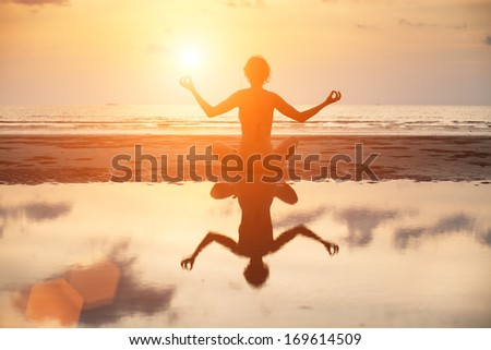Yoga woman sitting in lotus pose on the beach during sunset, with reflection in water in bright colors. - stock photo