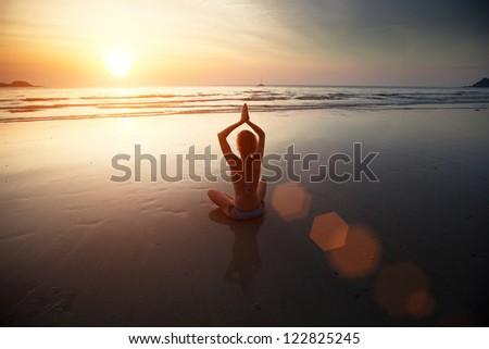 Yoga woman sitting on sea coast at sunset - stock photo