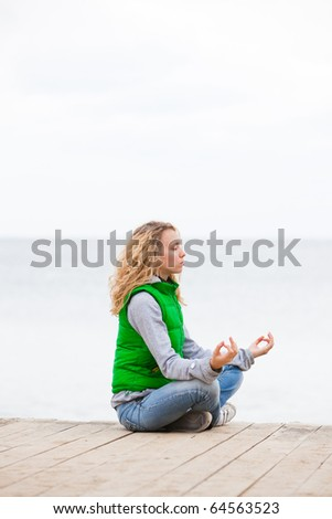 Yoga woman sitting on wooden bridge near the ocean - stock photo
