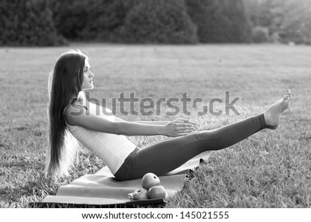 yoga woman with apples on green grass. Outdoor/ Black and white - stock photo
