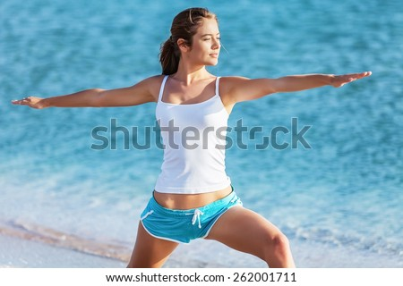 Yoga. Yoga woman in zen meditating in warrior pose relaxing outside by beach at sunrise or sunset. Female yoga instructor working out training in serene ocean landscape. Big Island, Hawaii, USA. - stock photo