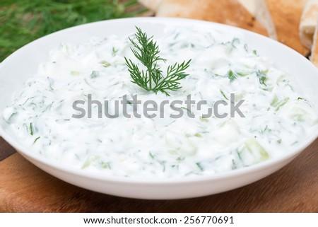 yoghurt sauce tzatziki with herbs, cucumber and garlic, close-up - stock photo